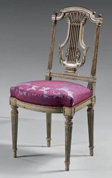 Chaise à dossier ajouré, en noyer mouluré et sculpté d'une lyre. Les dés à réserve....
