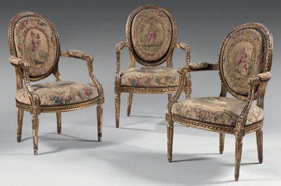 Trois fauteuils à dossier cabriolet, en bois sculpté et doré, à décor d'encadrement...