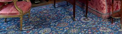 Important tapis mécanique, dans le goût persan, à fond bleu, à décor de larges rinceaux...