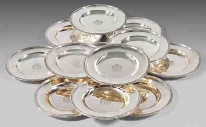 Suite de douze assiettes rondes en argent à bord mouluré gravé en leur centre des...