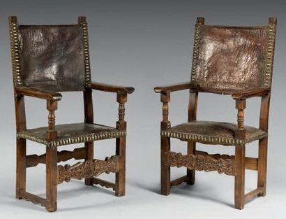 Paire de fauteuils en noyer sculpté, assises et dossiers tendus de cuir retenu...
