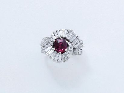 Bague en or gris 18 K, ornée d'un rubis ovale facetté dans un tourbillon de diamants...