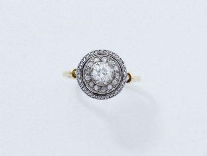 Bague en or 18 K et platine, centrée d'un diamant taille ancienne en serti griffe...