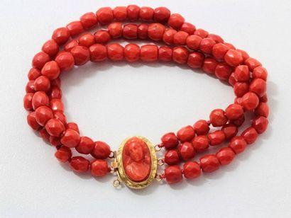 Bracelet composé de 3 rangs de perles de corail facetté, centré d'un fermoir à cliquet...