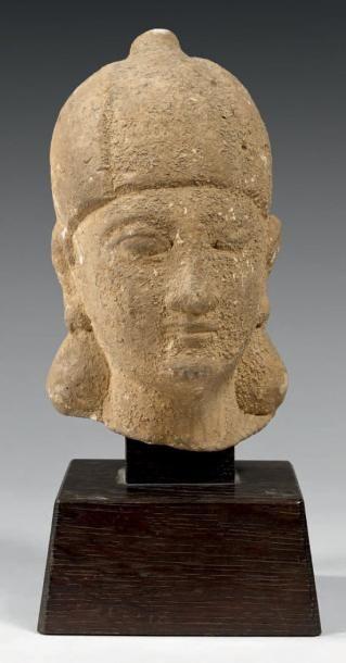 Tête féminine portant un haut bonnet côtelé. Calcaire avec dépôt calcaire. Chypre,...