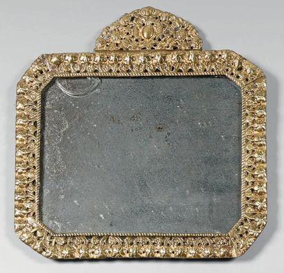 Glace dans un cadre en bronze ajouré et doré,...