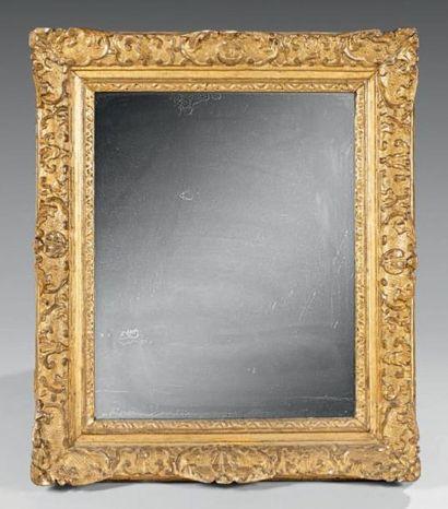 Glace dans un cadre en bois sculpté et doré,...