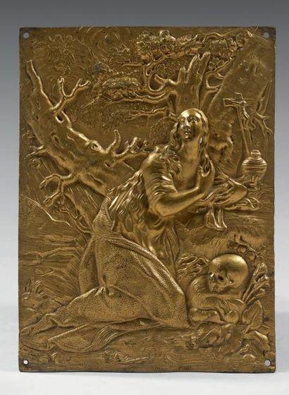 Plaque rectangulaire en bronze ciselé et doré, figurant une sainte pénitente agenouillée...