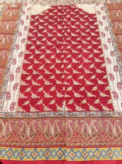 Panneau en coton imprimé fond rouge,  bordures à décor polychrome de bothés.  Composé...