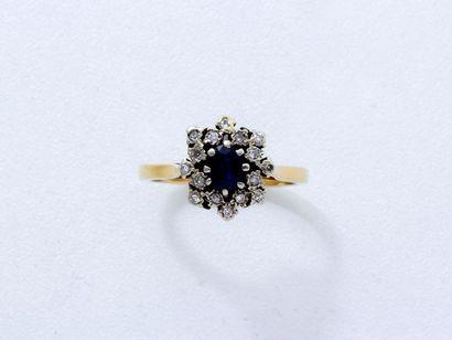 Bague en or 18 K, ornée d'un saphir ovale facetté en serti griffe, entouré de diamants...