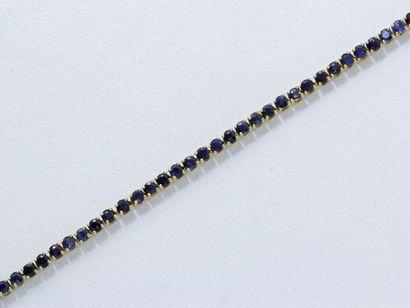 Bracelet articulé en or 18 K, orné d'une ligne de saphirs ronds facettés en serti...