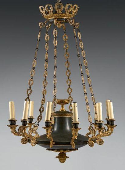 Lustre à douze lumières en bronze ciselé, doré ou patiné; la couronne à cornes fleuries...