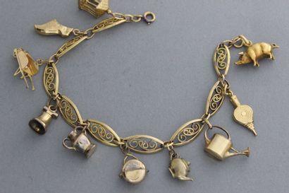 Bracelet en or enrichi de breloques, certaines...