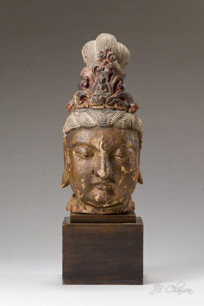 CHINE : Tête de Guanyin en bois laqué. Le visage serein, les yeux mi-clos incrustés...