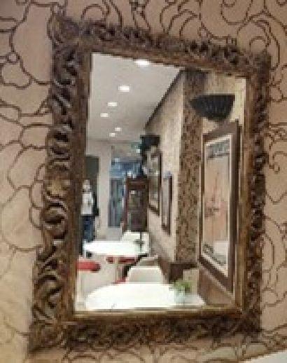 Miroir en bois sculpté et ajouré à décor de feuillage.  H.: 120 cm; L.: 90 c...