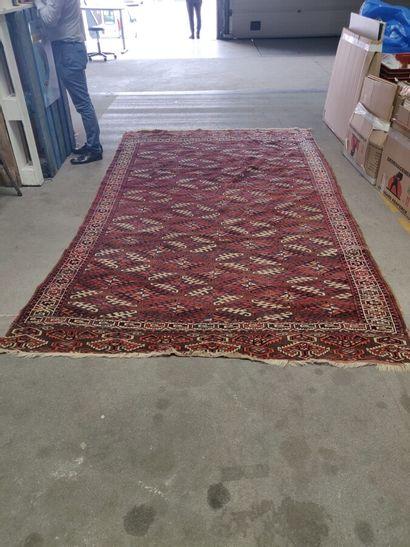 Grand tapis Boukhara fond rouge, motifs losangiques....