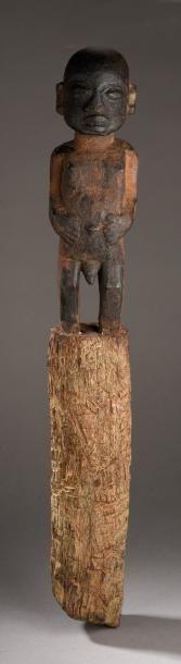 STATUE POTEAU. Bois sculpté dans sa partie supérieure d'un homme debout, les mains...