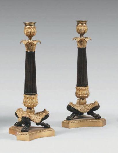 Paire de bougeoirs en bronze doré et bronze patiné. Fût cannelé, base tripode à...