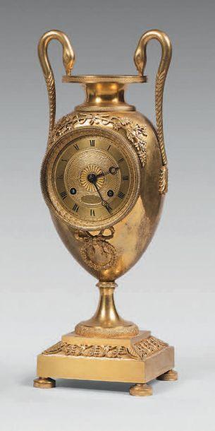 Pendule en forme d'urne en bronze doré à...
