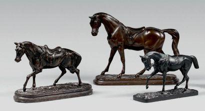 Trois statuettes de chevaux sellés au pas,...