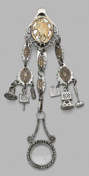 Châtelaine en métal doré et argenté à décor d'attributs en applique, à trois brins...