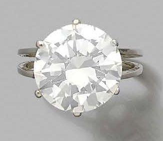 Bague en or gris 750 millièmes, ornée d'un diamant solitaire de forme ronde et de...