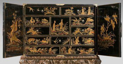 Grand cabinet en laque européenne orné de paysages animés dorés sur fond noir ouvrant...