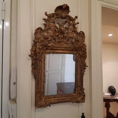 Miroir dans un encadrement en bois doré à fronton ajouré sculpté d'une grenade et...