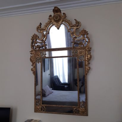 Rectangular mirror in a double frame with spandrels and pediment in gilded wood...
