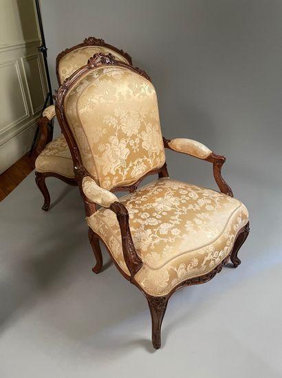 Suite de six fauteuils à dossier plat en noyer sculpté et ajouré de fleurs. Epaulements...