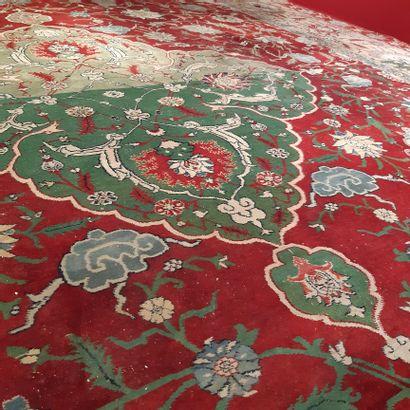 Grand tapis orné d'un médaillon polylobé vert sur un fond rouge à écoinçons, orné...