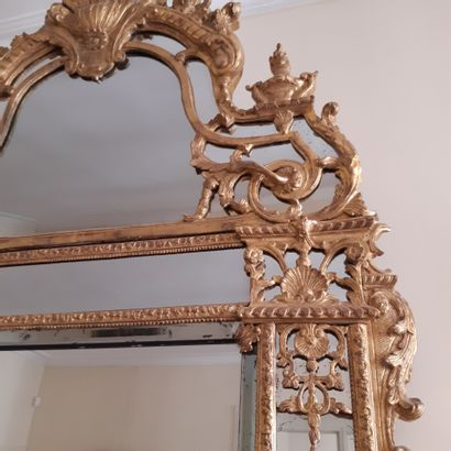 Bevelled mirror in a double frame with a pediment in gilded wood carved with shells,...
