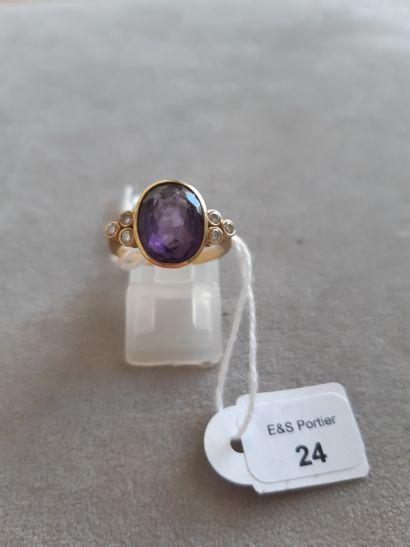 Bague en or jaune 750 millièmes ornée d'une pierre de synthèse violette (verre)...