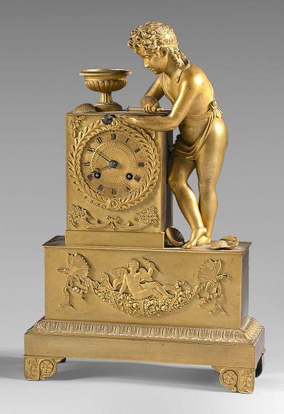 Pendule en bronze doré représentant un enfant...