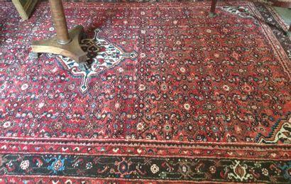 Tapis persan à décor herati sur fond rouge...
