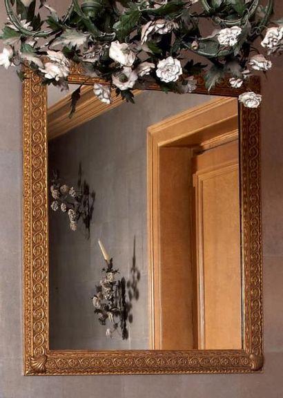 Miroir dans un encadrement en bois doré sculpté...