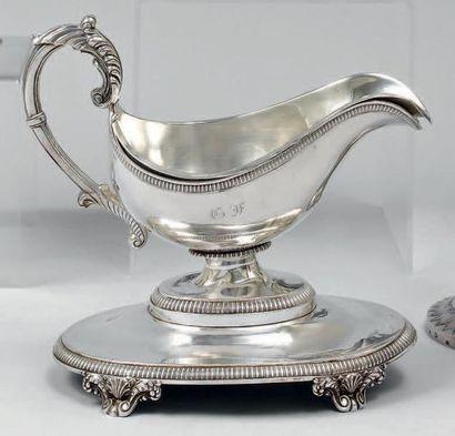 Saucière casque monogrammée, sa doublure et son présentoir en argent décorés de...