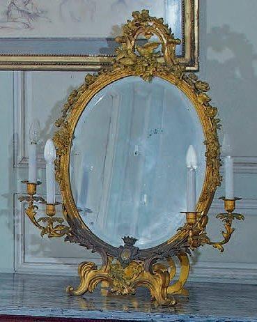 Miroir en bronze doré de forme ovale, comprenant...