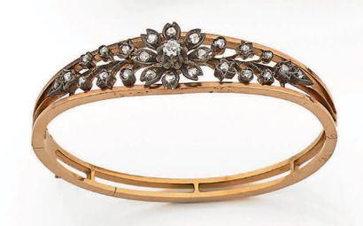 Bracelet rigide et ouvrant en or jaune 750 millièmes orné d'un motif fleur au centre...