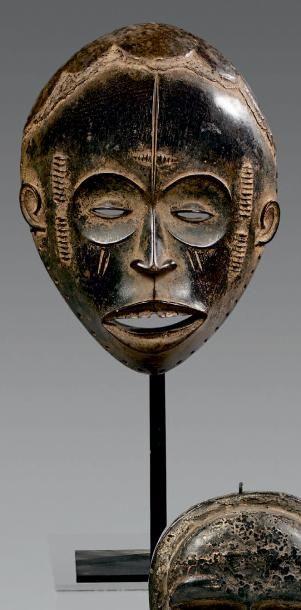 Masque Igbo, Nigeria. Bois à patine brun noir en partie brillante. Hauteur: 23,...