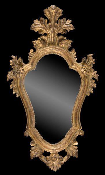 Miroir en bois doré de forme mouvementée...