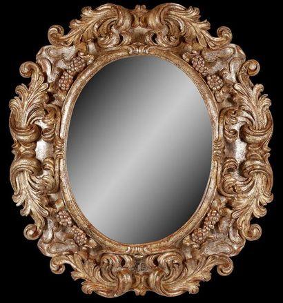 Grand miroir ovale en bois argenté et doré...