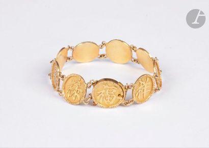 Bracelet en or jaune 18K (750) articulé de pastilles, chacune ciselée d'un idéogramme....