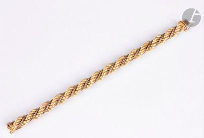 Bracelet torsadé en or jaune 18K (750) strié et cordelette d'or gris 18K. Longueur...