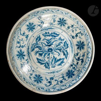 VIETNAM - XVe siècle Plat rond en grès émaillé en bleu sous couverte de lotus. (Restaurations)....