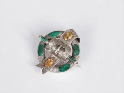 Broche en argent de forme circulaire, centrée d'une ceinture stylisée ornée d'une...