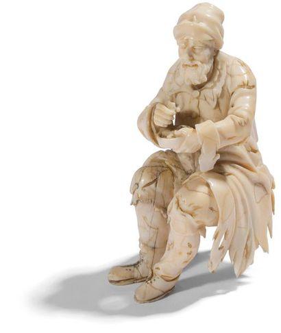 Mendiant en ivoire sculpté en ronde-bosse....