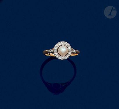 Bague en or 18K (750), ornée d'une perle bouton sans doute fine entourée et épaulée...