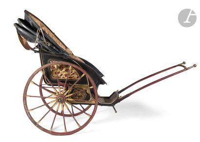 Important pousse-pousse en bois peint et richement décoré, avec sa capote en cuir...