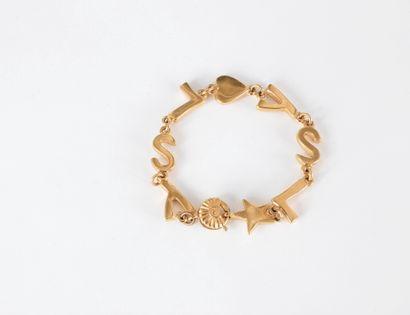 YVES SAINT LAURENT.  Bracelet en métal doré...
